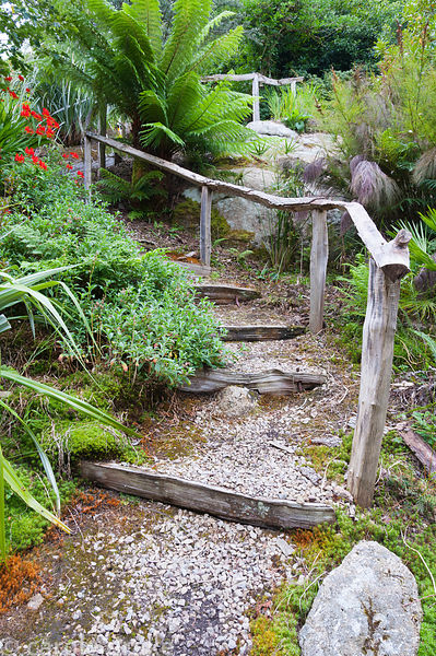 Riven oak handrails snake up the steepiy sloping garden beside shallow steps, past large granite outcrops surrounded by lush ...