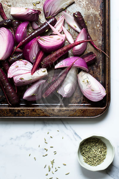 Purple onions and purple carrots on a metal tray, with olive oil and sprinkled with fennel seeds, ready for the oven. The sur...