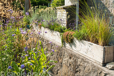 Wooden trough decorated with simple circles of drilled holes, planted with grasses, lavender and herbs. The 'Garten' Garden, ...