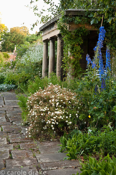 Blue delphiniums frame a stone summerhouse. Whalton Manor Gardens, Whalton, Northumberland, UK