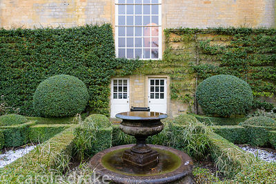 The Fountain Court with a central water feature set inside box-edged beds, framed by clipped box and walls covered with train...