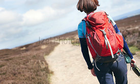 A closeup view of a female hiker walking along a trail on the moors with a red backpack on an autumn day in Blanchland, Count...