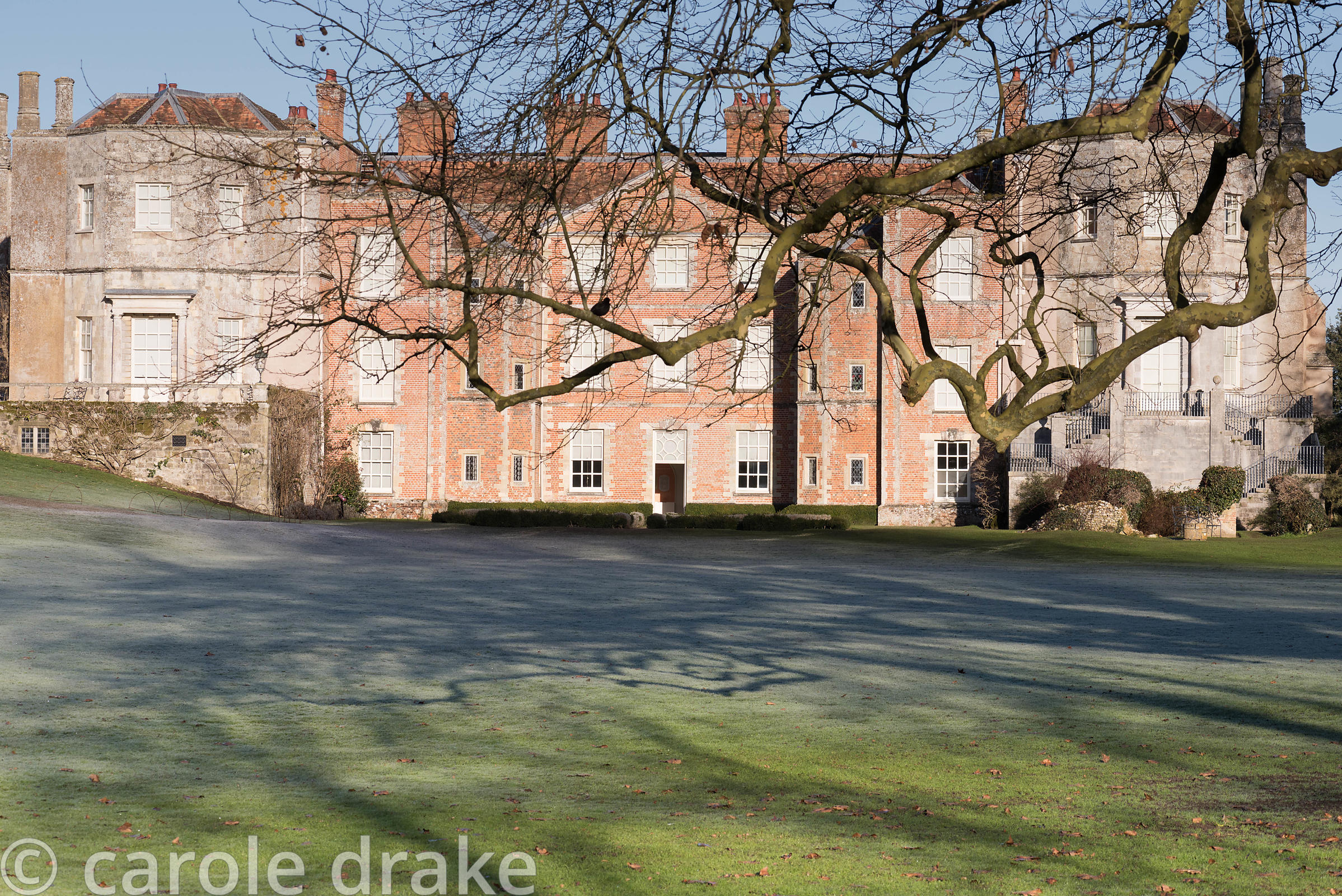Facade of Mottisfont house with frosted lawn patterned with shadow in January