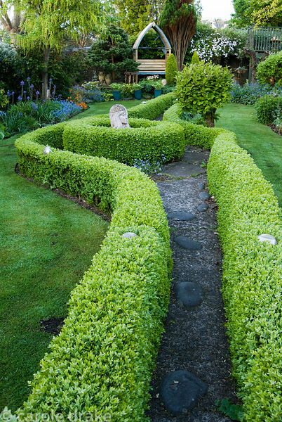 Box hedges edge the central path that leads through the first section of this 250' long garden, featuring stone statuary and ...