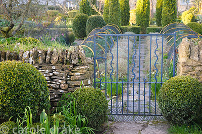 The gate into the potager framed with clipped box at Barnsley House, Cirencester, Glos, UK