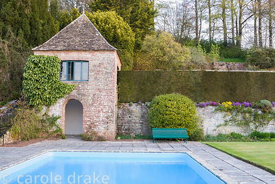 Swimming pool added to the garden in 1967, with terraces rising behind constructed in the early 20th century, summerhouse bui...