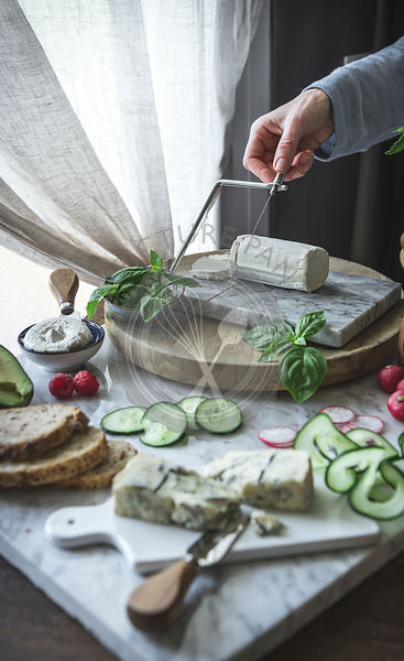 A woman slicing soft cheese on a cheese board, with various vegetables.