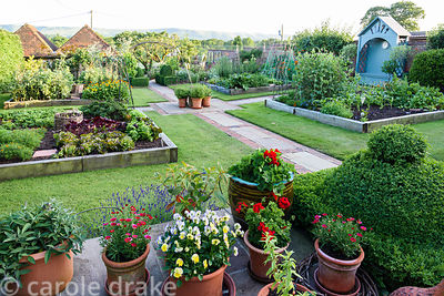 Kitchen garden divided into quarters with raised beds edged with railway sleepers, metal arches and obelisks with a central a...