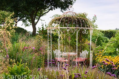 Gravel garden with metal gazebo and late season perennials and grasses in rural Nottinghamshire in September. Planting includ...