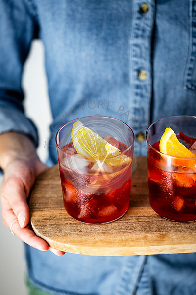 Negroni cocktail on a wooden tray, held by a person in a denim shirt