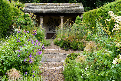 The herb garden with clipped yew spheres around a central circle set with a mill stone, and lush planting including fennel, a...