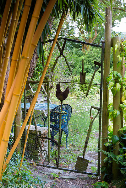 Bamboo frames a decorative metal gate using old tools and a metal hen at Five Oaks Cottage in July