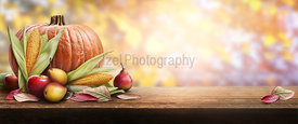 A thanksgiving celebration table of pumpkins, apples, pears and corncobs with autumn sunset foliage in the background.