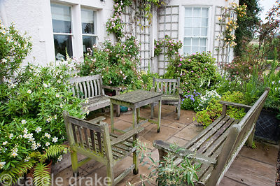 Seating area on stone terrace beside the house surrounded by roses. Mindrum, nr Cornhill on Tweed, Northumberland, UK