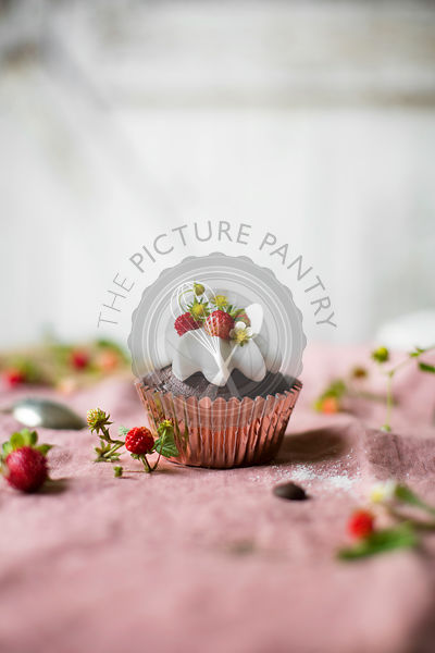 Chocolate cupcake with wild strawberries on the table