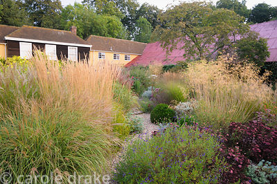 Gravel path leading into the central circular bed framed by miscanthus, Stipa gigantea, Sedum 'Purple Emperor', salvias and C...