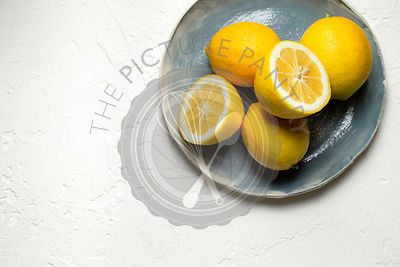 Fresh lemons, whole and sliced in half, arranged on a blue hand made plate.