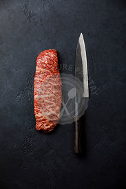 Raw fresh marbled meat Steak Wagyu beef and kitchen knife on dark background