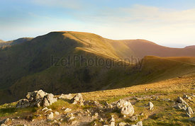 The warm evening glow as sunset approaches over the summit of High Street and the old Roman Road with Thornthwaite just to th...