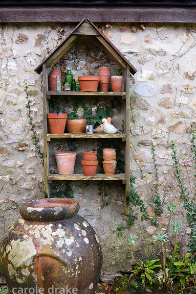 Outdoor shelf display with terracotta pots, glass bottles and small birds