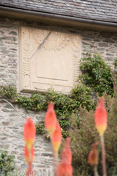 Carved sundial on the front of the house framed by red hot pokers. Coleton Fishacre, Kingswear, Devon, UK