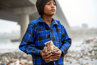 Young ragpicker and discardrd statue