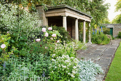 Roses and blue delphiniums frame a stone summerhouse. Whalton Manor Gardens, Whalton, Northumberland, UK