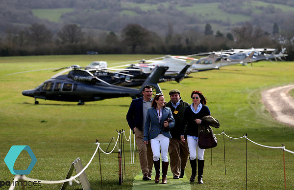 Racegoers make their way across the field as they arrive at the course by helicopter during Gold Cup Day of the Cheltenham Fe...