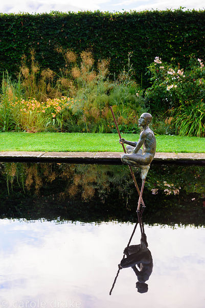 Sculpture of a naked man crouching on a reflecting pool in the bronze garden at the Yeo Valley Organic Garden, Blagdon, Somer...