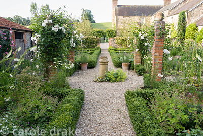 Courtyard garden laid out with low box hedging and brick pillars planted with Rosa 'Iceberg' and clematis with pots of lilies...