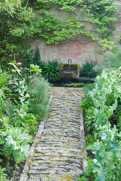Stone path leads to small water feature between beds with hot colours in late summer including tithonia, Dahlia 'David Howard...