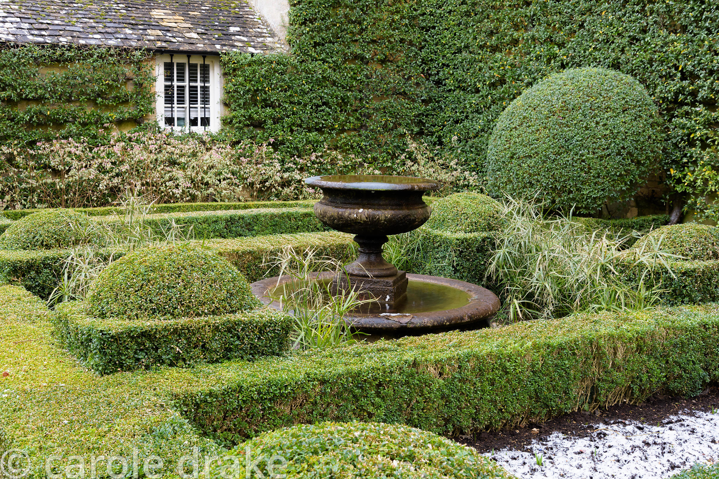The Fountain Court with a central water feature set inside box-edged beds, framed by clipped box, Fuchsia magellanica 'Varieg...