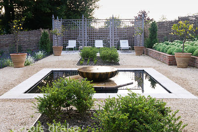 Newly planted Persian garden with a central pool, screened seating area and formal planting including squares of box and Ilex...
