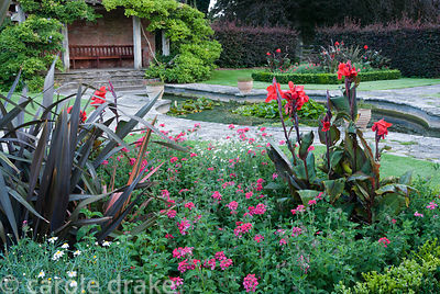 Red Garden has a formal lily pond at its centre and box edged beds planted with scarlet flowered cannas, verbenas and Phormiu...