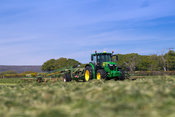 Contractor rowing up grass for silage with a Krone Swadro rake pulled by a John Deere 6145R, Lancaster, Lancashire, UK.