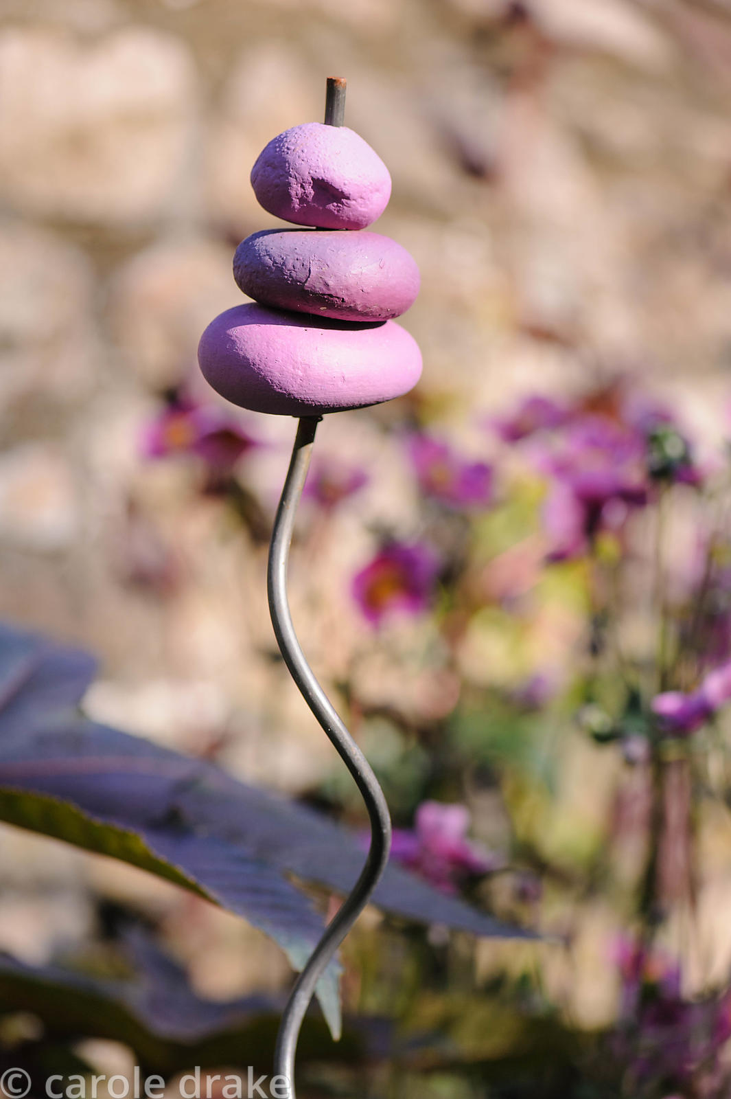 Decorative feature made of purple painted pebbles threaded onto a metal rod.