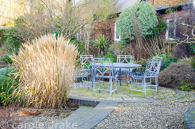 Seating area at the back of the house surrounded by planting including grasses such as Miscanthus sinensis 'Yakushima Dwarf' ...