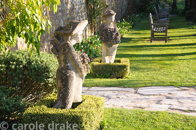 A pair of sculptures by Simon Verity frame a gate out of the main garden giving access to the potager beyond. Barnsley House,...