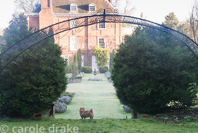 A rose arch frames the central axis of the Rose Garden, to the south of the house at Welford Park, Welford, Newbury, Berkshir...