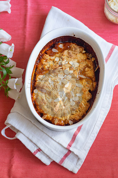 Plum cobbler with almond flakes and cream