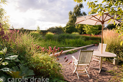 Seating under an umbrella near a naturalistic pond with a contemporary solid edge on one side at Farlands, Tenbury Wells in A...