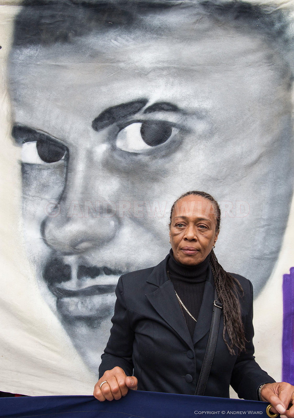 Stephanie Lightfoot-Bennet twin sister of Leon Patterson who died in police custody, in front of a banner portrait of Mark Du...
