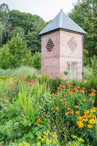 Dovecote, built in 2007, with hot colours of heleniums and rudbeckias in the foreground. Rhodds Farm, Kington, Herefordshire, UK