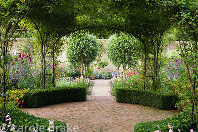 Rose arches at the centre of the walled garden are clothed with Rosa banksiae, clipped box hedges define the space below. Had...