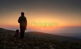 A hiker and their dog watching the bright orange sunrise over Bampton Common from the summit of Rampsgill Head in the Lake Di...