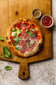 Pepperoni Pizza on wooden cutting board on stone travertine background