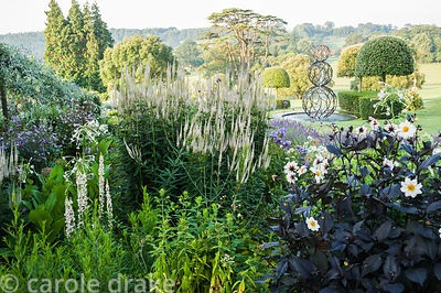 Box edged beds at the top of the double summer herbaceous borders designed by Xa Tollemache feature dark leaved Dahlia 'Twyni...