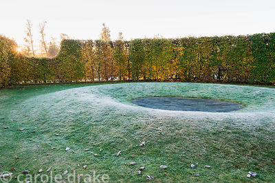 Hornbeam hedge illuminated by dawn sunlight with doughnut-like landform set with a slate centre in desginer Brita von Schoena...