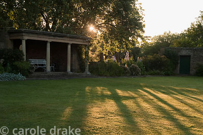 Early morning sun spreads across the lawn in front of the stone summerhouse. Whalton Manor Gardens, Whalton, Northumberland, UK