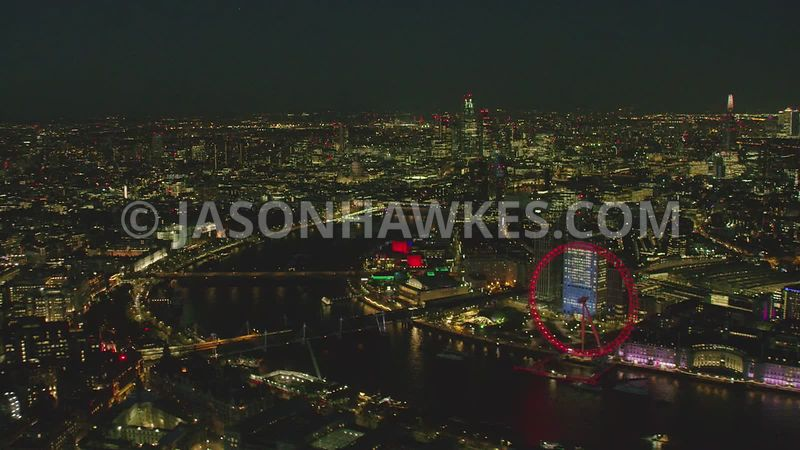 Night aerial helicopter footage of the London Eye, River Thames and Southbank, London.